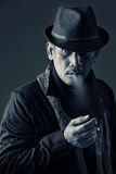 Old detective smoking a cigarette Stock Image
