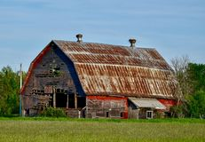 Old Deteriorating Barn. This is a Summer picture of an old deteriorating dilapidated red barn with a metal roof located in Schoolcraft County, Michigan in the stock photography