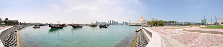 The old Dhow Harbor at the Doha Corniche, Qatar. A panoramic view of the Dhow Harbor in Doha, Qatar, with the Museum of Islamic Art, Dhow (old-style fishing boat Royalty Free Stock Photo