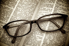 Old dictionary and black glasses Royalty Free Stock Images