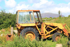 An old digger rusting in the weeds. Stock Image
