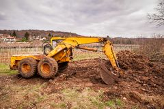 Old yellow earthmover. Old digger used to move and load manure in agriculture Royalty Free Stock Photos