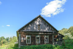 Old dilapidated abandoned wooden house on forest clearing Stock Photo