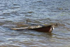 Old dilapidated boat on the water tied with iron chain with lock to the shore. stock photos