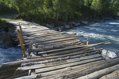 Old dilapidated bridge on the mountain river. Stock Photography