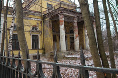 Old dilapidated building with a fence. Main entrance of the old dilapidated building with a fence Stock Photo