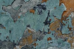 Old dilapidated exterior concrete wall with peeled off multicolor paint. Macro photo of old dilapidated concrete exterior wall painted in multicolor peeled off stock images