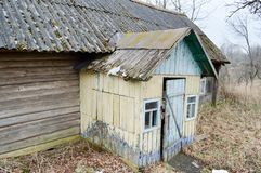 The old dilapidated porch, the entrance to the wooden village house and the wall of dilapidated logs of an abandoned village house. In the wilderness Stock Photos