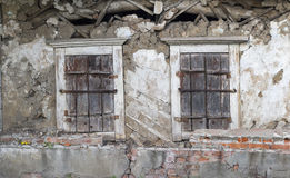 Old dilapidated wall with two shuttered windows.  Stock Photography