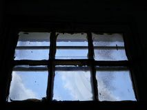 Old and Dilapidated Window With Square Panes. Rough and textured glass, and blue sky in the background.  Symbol or metaphor for urban or rural decay royalty free stock photography