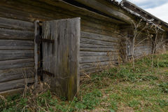 Old dilapidated wooden house. With an open door Stock Photos