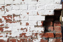 Old,dilapitated brick wall, with some cracked and others missing. Old, weathered brick wall painted white, with several cracked bricks and others missing Royalty Free Stock Photo