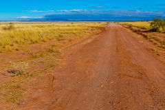 Old Dirt Road Heading to Nowhere in New Mexico. Old Dirt Road Heading Out in the Wild Desert Landscape of New Mexico with Mountains in the Distance Royalty Free Stock Photos