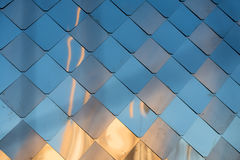 Old, dirty aluminum metal wall facade panel with rhombus, similar to the scales and tiles. Reflection of sunset. Royalty Free Stock Photography