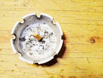 Old dirty ash tray on a wood table. Dirty ash tray with a old cigarette in it. It is sitting on old wood table Stock Image