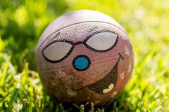 Old dirty ball with happy funny face on grass at sunny daylight.  Stock Images