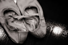 Old dirty ballet shoes on wood background | Ballerina used footwear Royalty Free Stock Photography