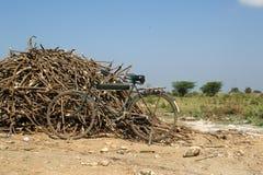 Old dirty bike around piles of firewood, Kerala, South India Stock Photos