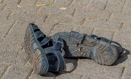 Old dirty black sandals thrown away royalty free stock photos