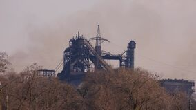 Old dirty blast furnace in smoke on metallurgical plant.
