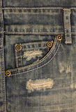 Old dirty blue jeans with holes and scrapes. Jeans pocket with bronze buttons. Rivets with sign JEANS in rim Stock Photography