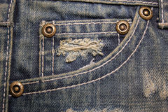 Old dirty blue jeans with holes and scrapes. Jeans pocket with bronze buttons. Rivets with sign JEANS in rim Royalty Free Stock Images