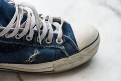 Old dirty blue sneaker. Teenager fashion. Old dirty blue sneaker with copyspace for text. Teenager fashion and lifestyle concept. Used ruin Footwear or shoes for royalty free stock image