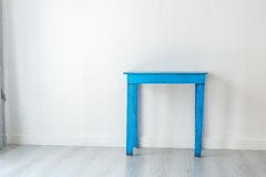 Old and dirty blue table in white room. Stock Image