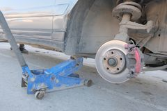 Close-up of a wheel arch without a wheel. Old dirty car hoisted on a jack. Tire installation or repair of the brake. Old dirty car hoisted on a jack. Close-up of stock image