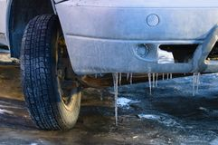 Old dirty car. Ice icicles on the bumper. stock images