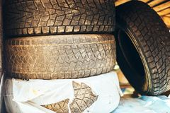 Old dirty car tires pile waiting winter summer tires. A pile of old, worn tires. They are dirty and the rims are rusty. The tire in the center is coated with royalty free stock photography