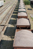 The old dirty cargo train with cars. Which are loaded by crushed stone Stock Images