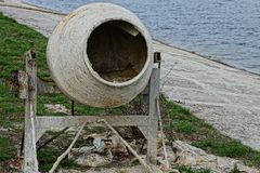 Old dirty concrete mixer stands on the street on the shore of the reservoir. Old, gray and dirty concrete mixer stands on the street on the shore of the Royalty Free Stock Photo