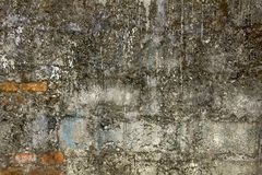 A old dirty concrete wall with protruding red bricks. uneven rough surface. stains of cement and paint. Old dirty concrete wall with protruding red bricks royalty free stock photo
