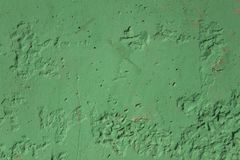 Old dirty damaged green concrete wall with scratches and black holes. rough surface texture. A old dirty damaged green concrete wall with scratches and black royalty free stock photo