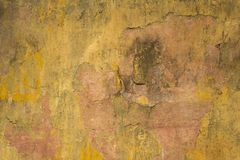 Old dirty damaged pink concrete wall with cracks and yellow shabby paint. rough surface texture. A old dirty damaged pink concrete wall with cracks and yellow royalty free stock image