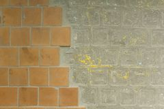 Old dirty damaged wall with brown orange ceramic tiles and gray cement with yellow paint stains. rough surface texture royalty free stock image