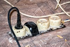 Old dirty extension cord. On dirty parquet stock image