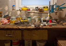 Old Dirty Garage Workbench. DUINO AURISINA, Italy - December 6, 2017: Very old dirty and messy garage workbench full of rusty tools, cans and boxes Stock Photography