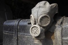 Old dirty gas helmet. Abandoned old dirty gas helmet hanging on rusty metal gas tank Stock Photography