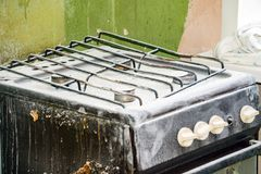 Old dirty gas stove in an abandoned state. An old dirty gas stove in an abandoned state. Unsanitary conditions Stock Images