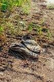 Old dirty grey sneakers abandoned on the ground Royalty Free Stock Photos