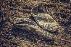 Old dirty grey sneakers abandoned on the ground Stock Photos