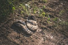 Old dirty grey sneakers abandoned on the ground. Royalty Free Stock Photos