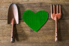 Old dirty grunge rusty gardening tools with heart shaped green leaf on dirty grunge wooden background Stock Image