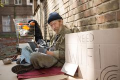 Old dirty homeless man holding laptop sitting on cardboard. Street life, tramp asking for free wi fi Stock Photography
