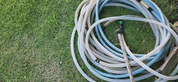 old dirty hose on green grass lawn royalty free stock images