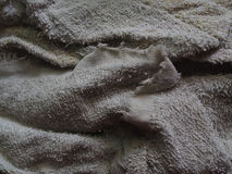 Old dirty kitchen cleaning towel cloth. Old dirty folded creased grey white kitchen cleaning towel cloth, full of dirt, in dark lighting Royalty Free Stock Image