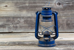 Old dirty Lantern on aged wood. Front view of an old dirty lantern on rustic wood Stock Photo