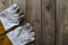 Old dirty leather work gloves on wood background Royalty Free Stock Image